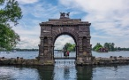 The welcome arch at the approach to Boldt Castle, with my crew! Note the tiny house island in the background.